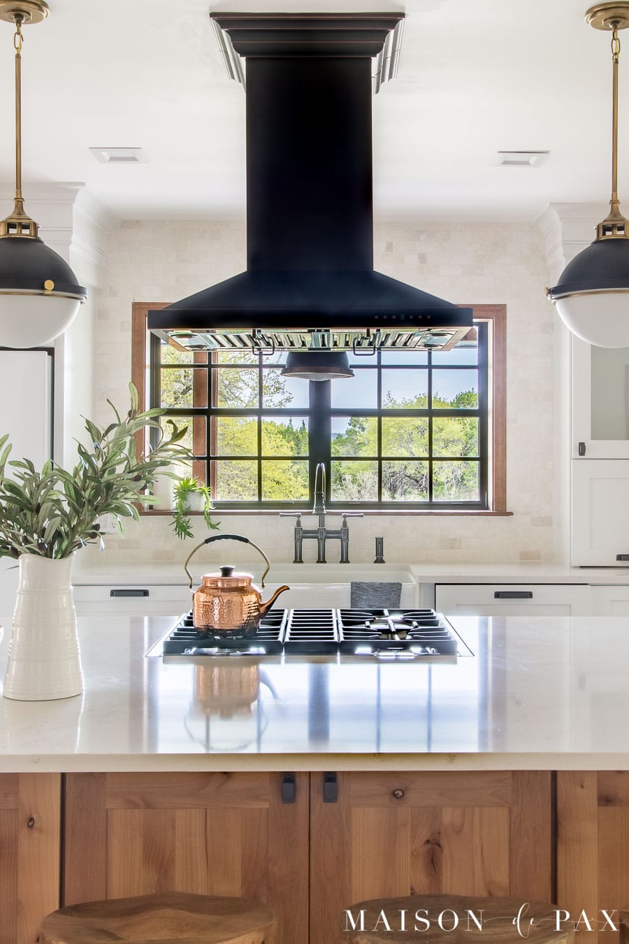 white counters and black range hood with white marble backsplash | Maison de Pax