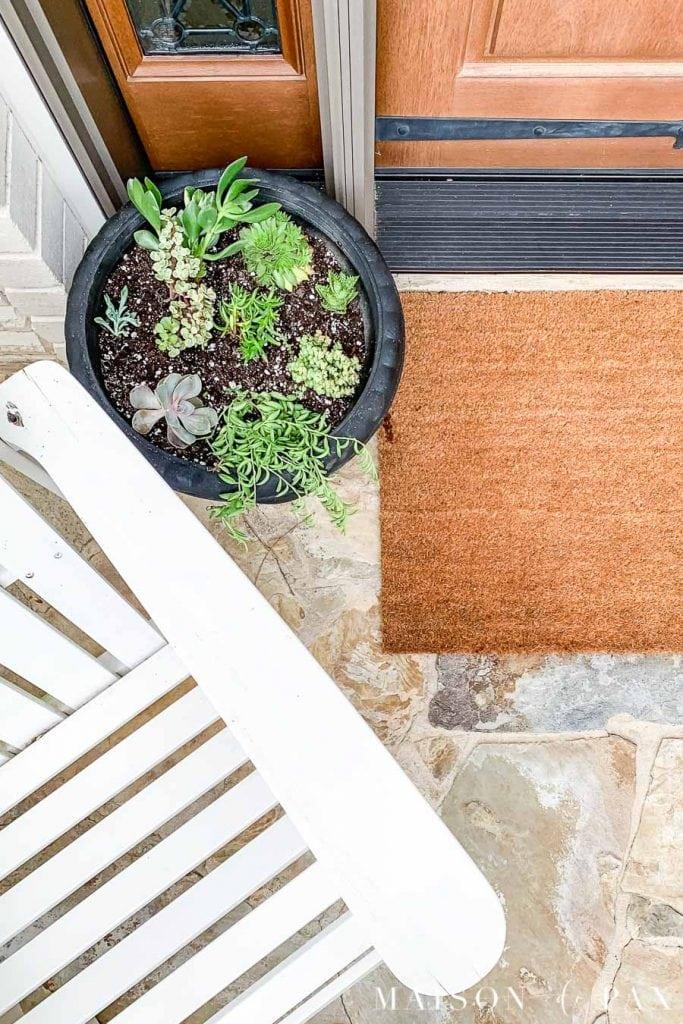 wood front door, brown door mat, black planter with succulents, and white adirondack chair | Maison de Pax