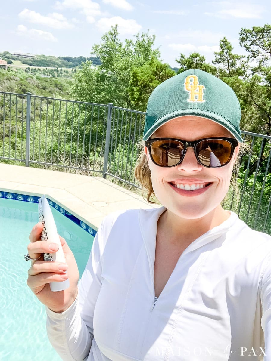 woman sporting hat, sunglasses, and long-sleeved swimwear for sun protection when pressure washing | Maison de Pax
