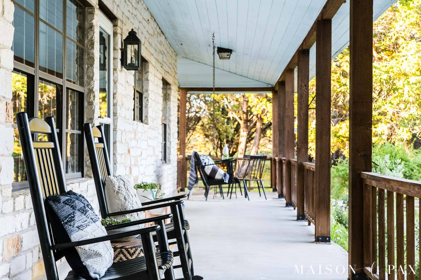black rocking chairs on a white Austin stone porch with brown cedar posts and railings | Maison de Pax