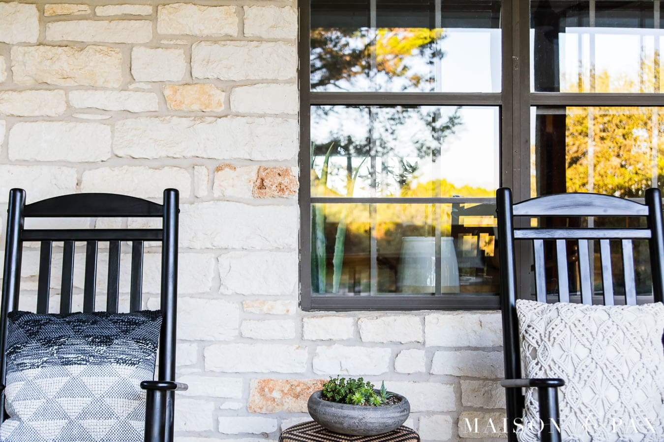 austin stone exterior with black windows and black rocking chairs on the porch | Maison de Pax