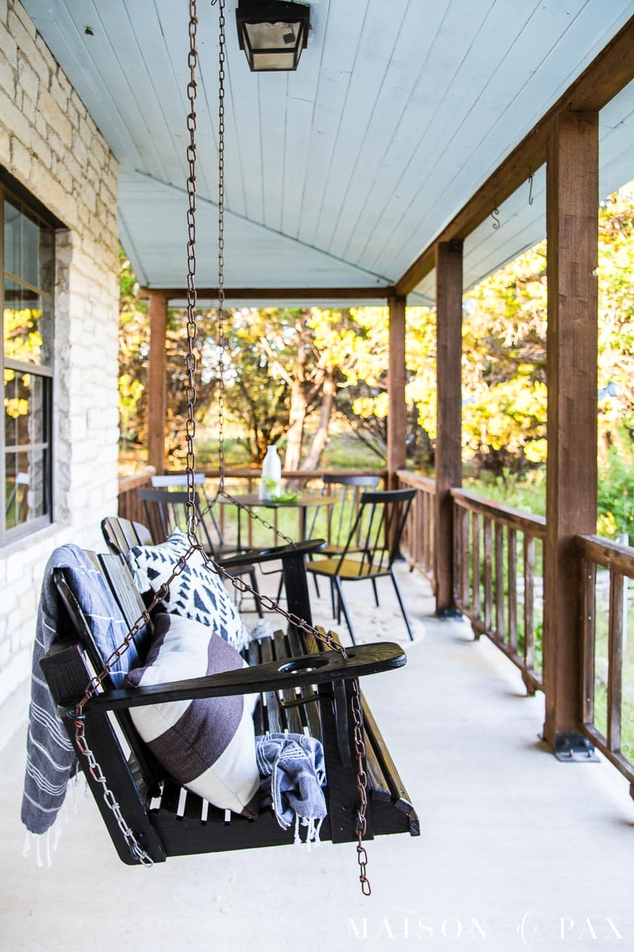 black wooden porch swing with black and white patterned pillows and black bistro set   Maison de Pax