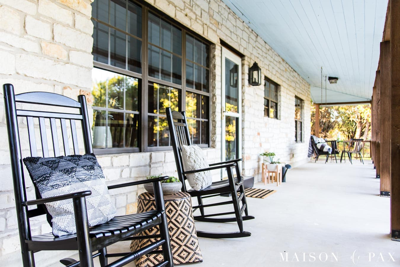 black rocking chairs on a porch with austin stone and black windows | Maison de Pax