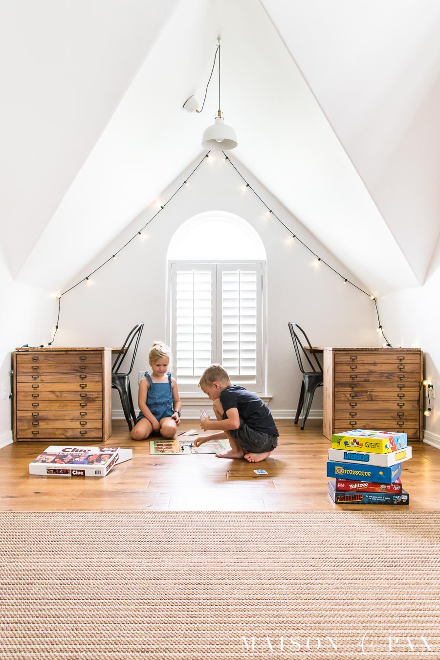 boy and girl playing board game on floor of playroom floor with peaked ceiling | Maison de Pax