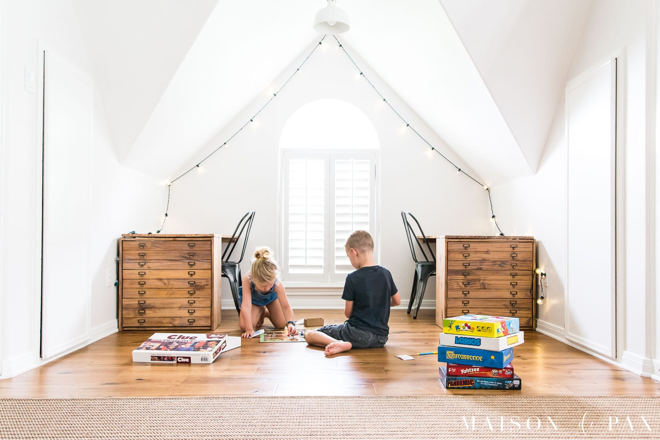 boy and girl in white room playing board game on floor | Maison de Pax