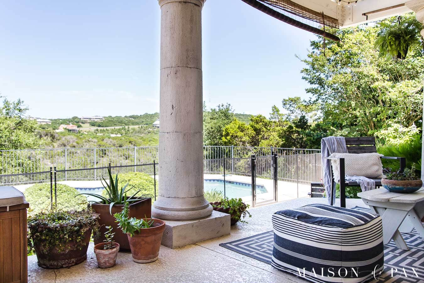 patio with large columns overlooking a pool and green hill country view | Maison de Pax