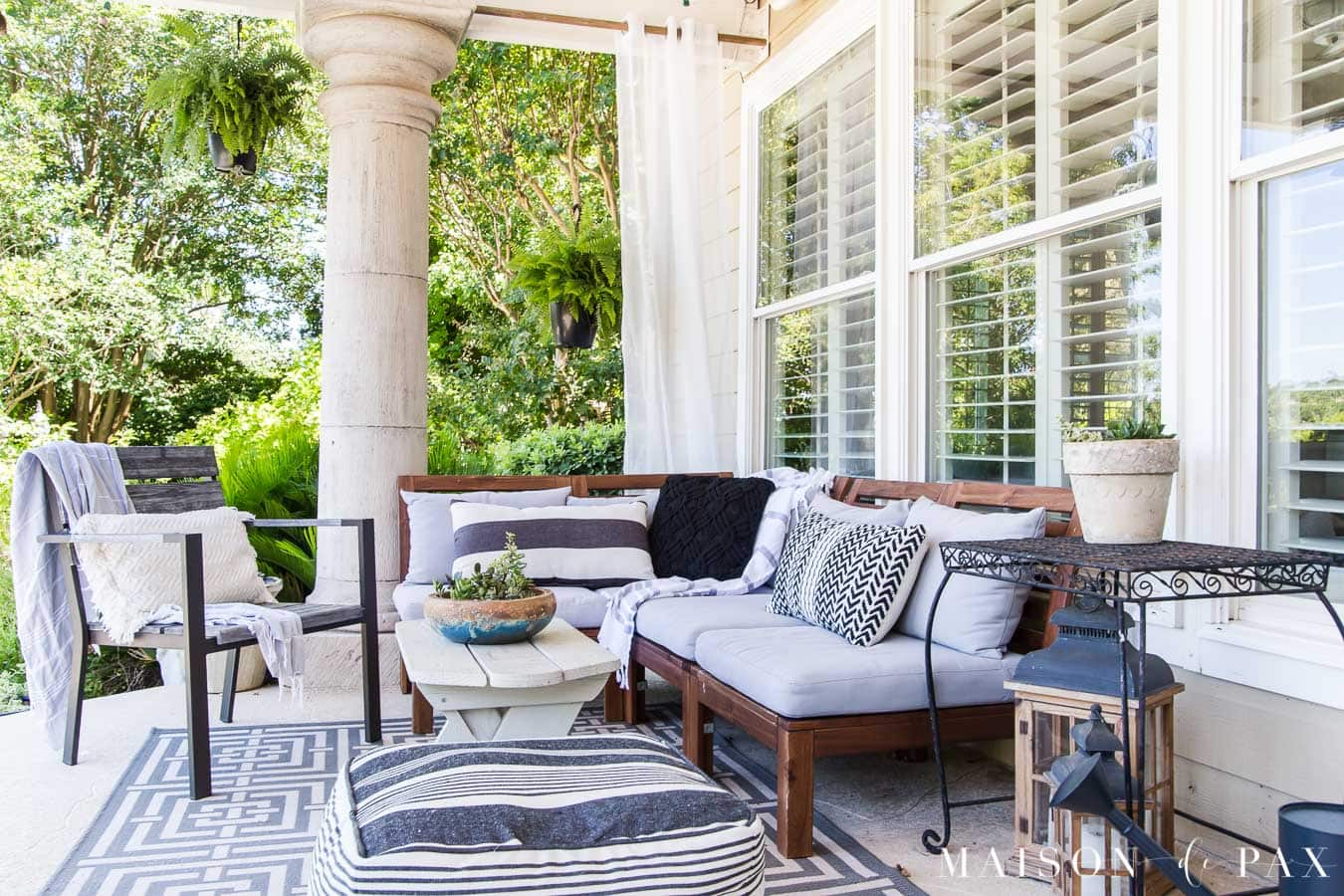 covered patio with large columns and wood furniture with cushions | Maison de Pax
