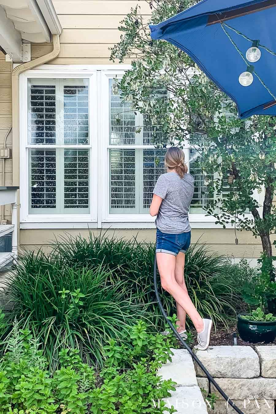 woman washing exterior windows with hose | Maison de Pax
