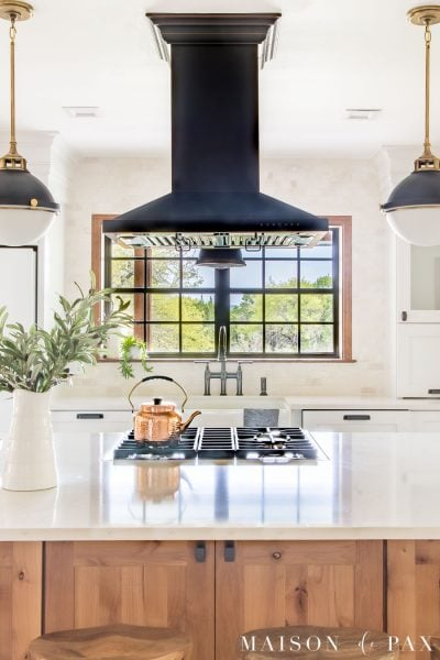 black framed window above farmhouse sink with black hood and white quartz counters | Maison de Pax