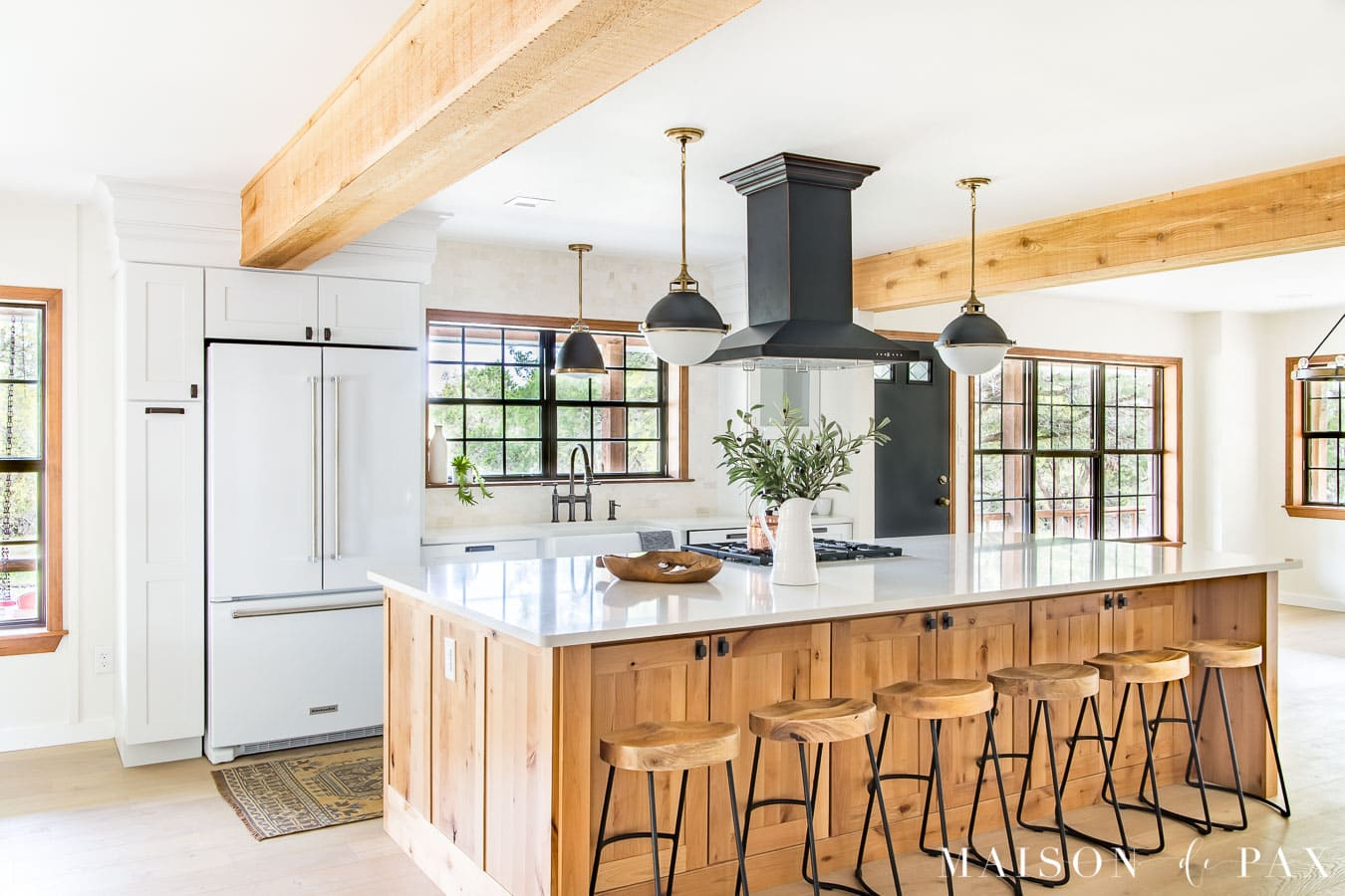 black framed windows in open kitchen with white walls and large wood island and wood beams | Maison de Pax