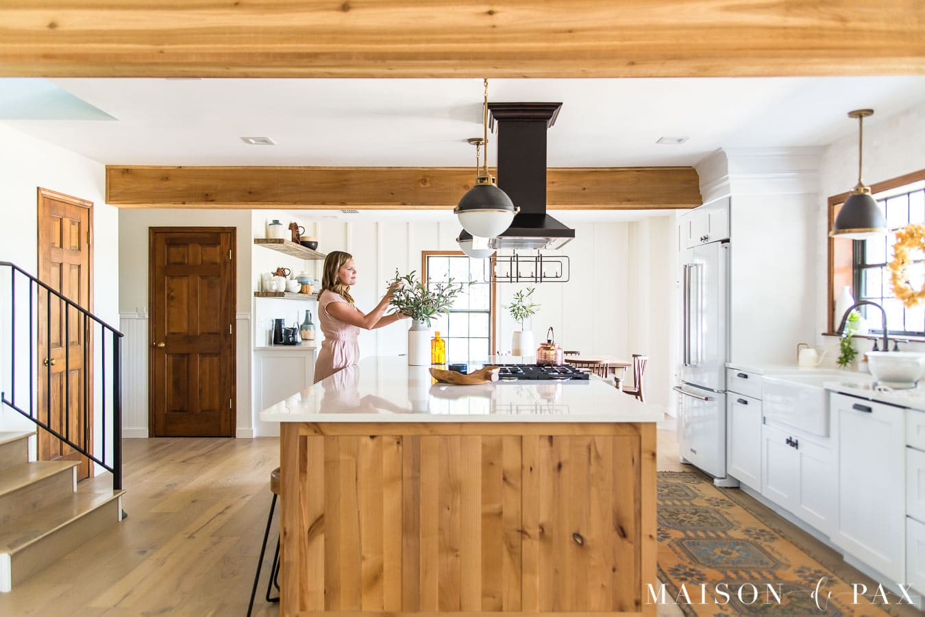 woman arranging fall foliage on kitchen island | Maison de Pax