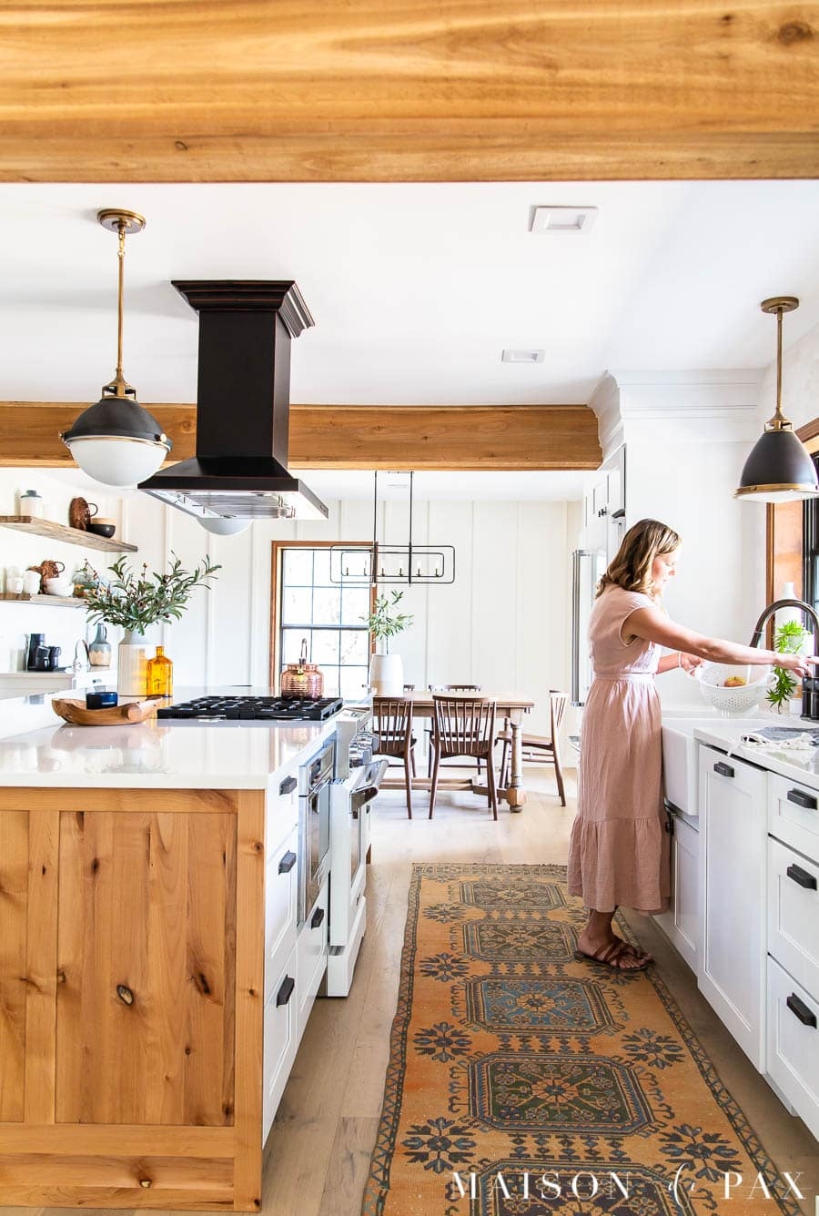 woman at sink in modern farmhouse kitchen with island | Maison de Pax