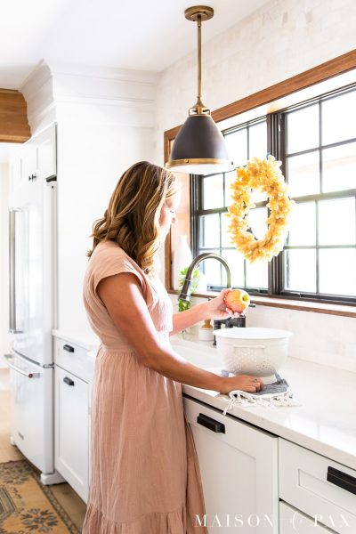 woman with apples in colander by sink | Maison de Pax