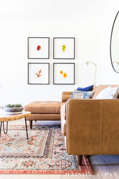 tan leather sofa with leaves in four black frames   Maison de Pax