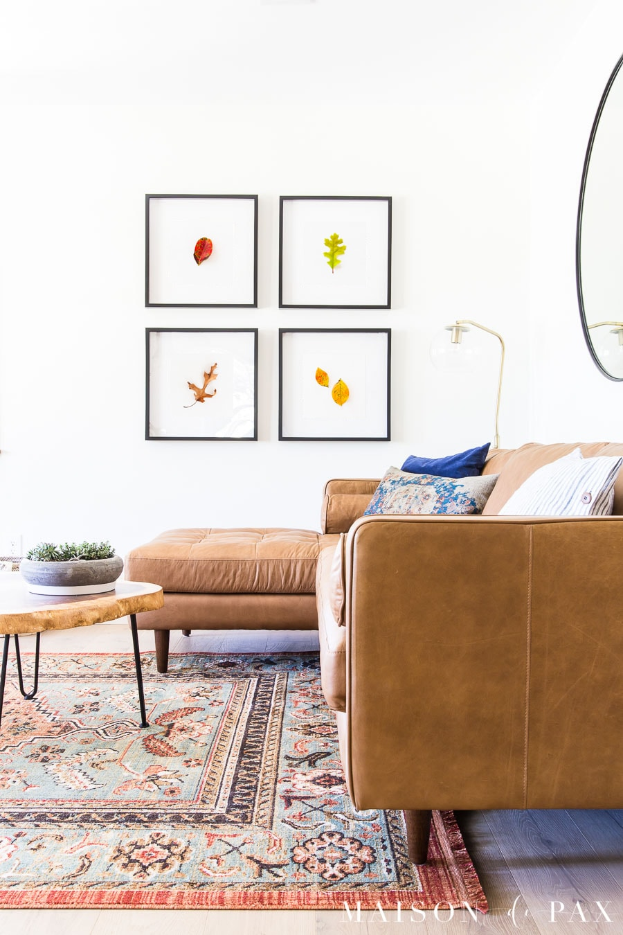 tan leather sofa with leaves in four black frames | Maison de Pax