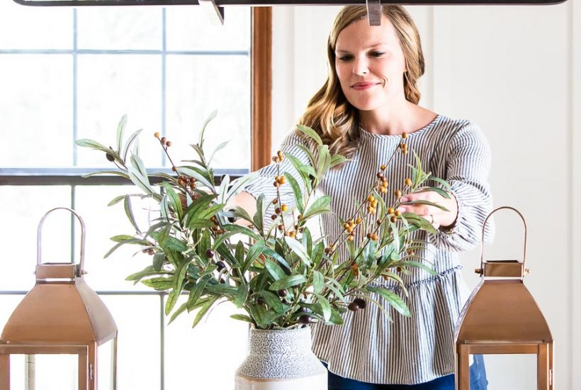 woman arranging greenery on table centerpiece | Maison de Pax