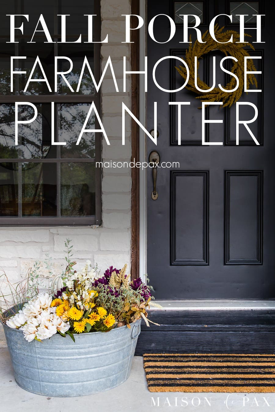 black front door with colorful planter beside | Maison de Pax