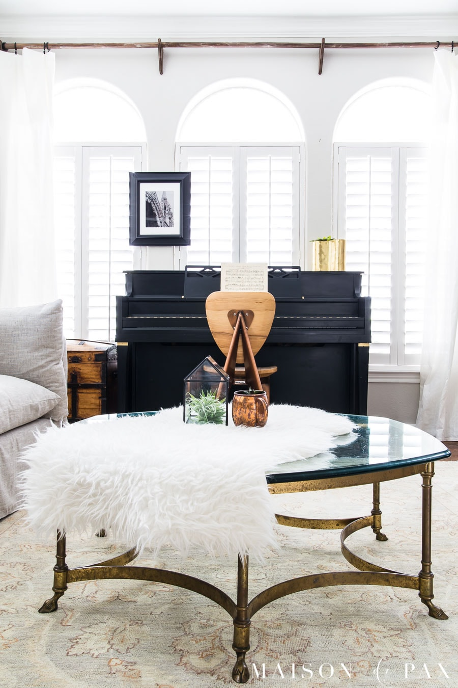 black piano, brass coffee table, faux sheepskin throw | Maison de Pax
