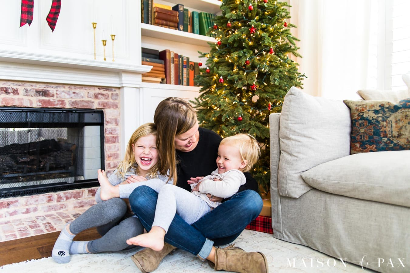 mother and daughters laughing in front of Christmas tree | Maison de Pax