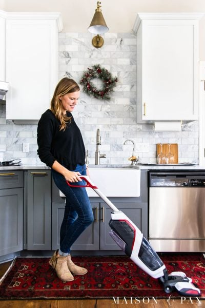 woman vacuuming rug in front of sink with christmas wreath on wall | Maison de Pax