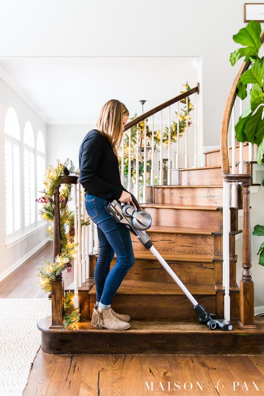 woman using cordless vacuum on stairs | Maison de Pax