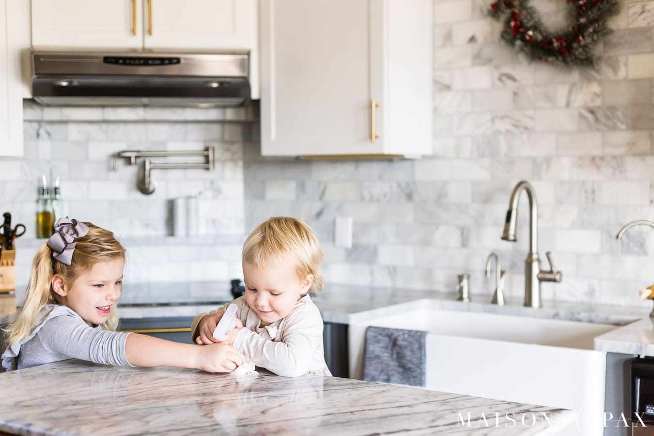 girls cleaning marble kitchen island counter | Maison de Pax