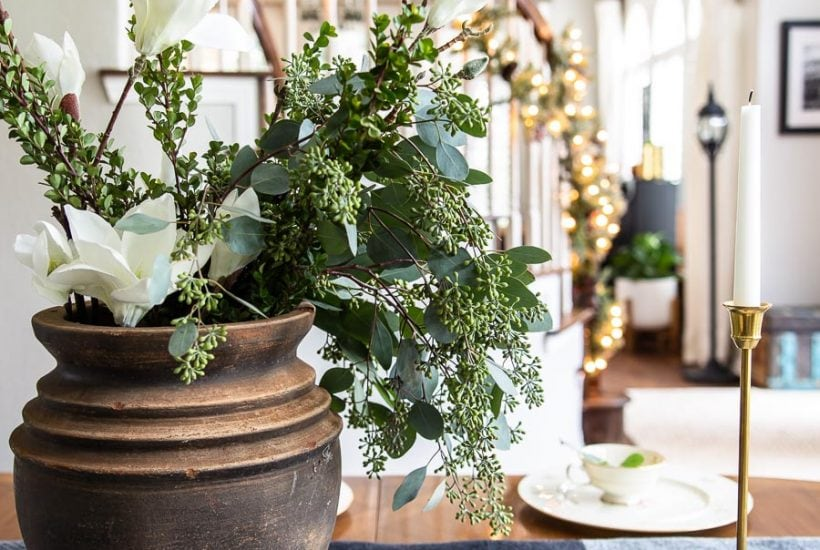 black pot with greenery and brass candlesticks holiday centerpiece | maison de pax
