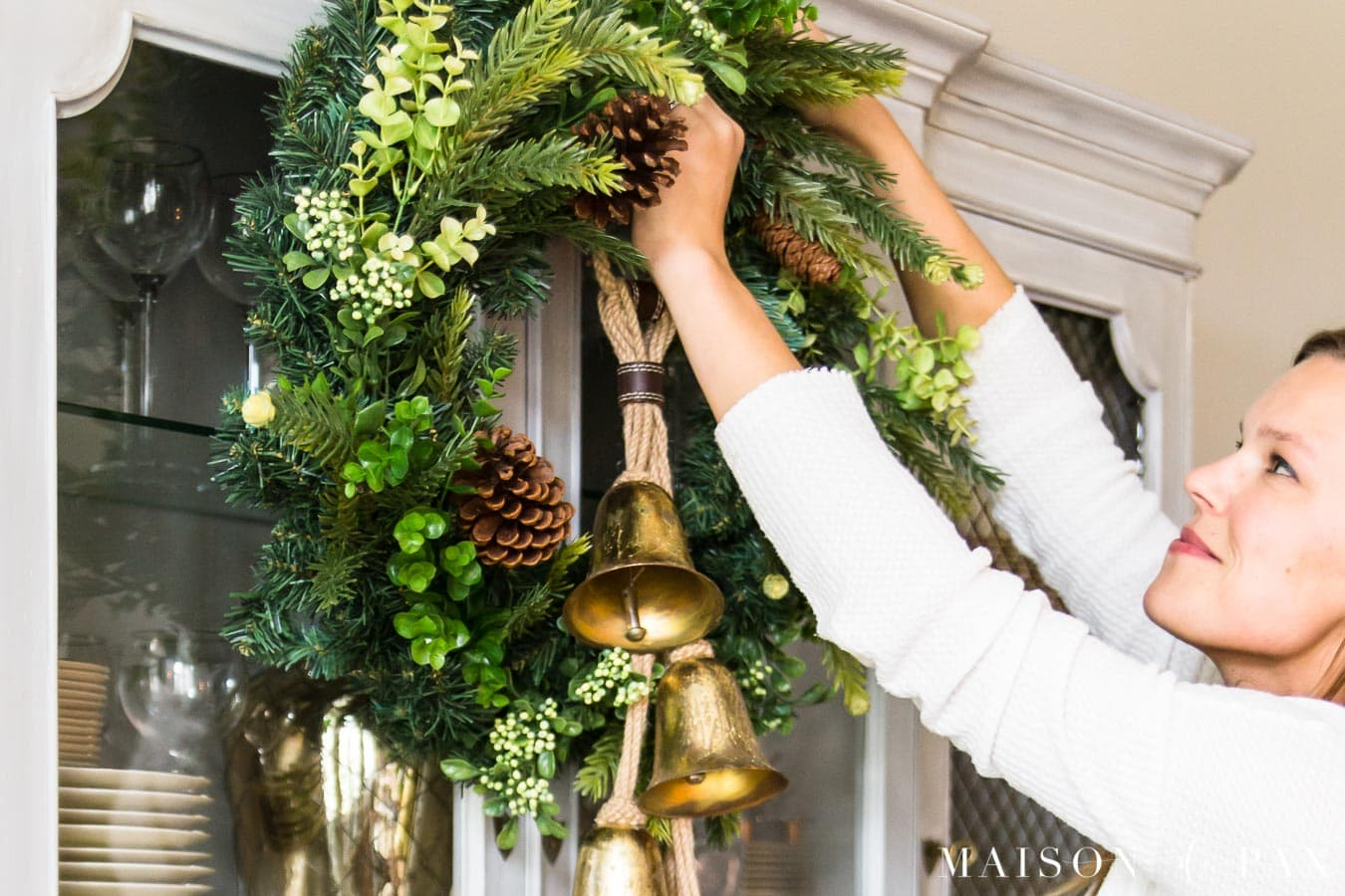 woman hanging greenery wreath with gold jingle bells | Maison de Pax