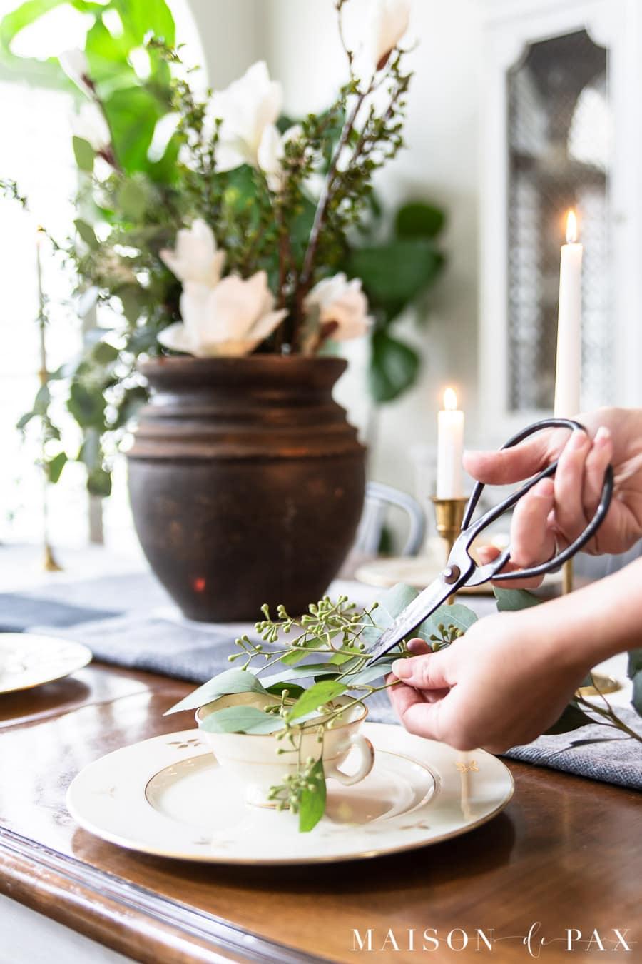 cutting eucalyptus clippings for teacups on plates | Maison de Pax