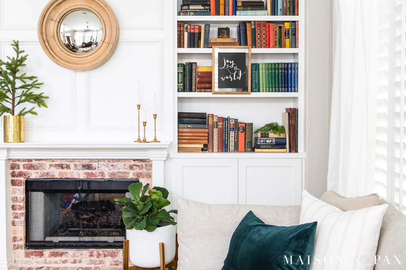 wall art hanging from bookcase beside fireplace | Maison de Pax