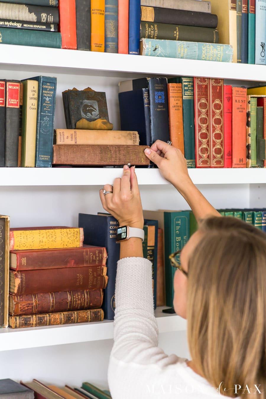 woman adding hook to bookcase   Maison de Pax