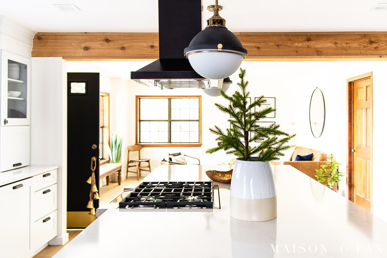 gold bells hanging on door knob and mini tree in crock on kitchen island | Maison de Pax
