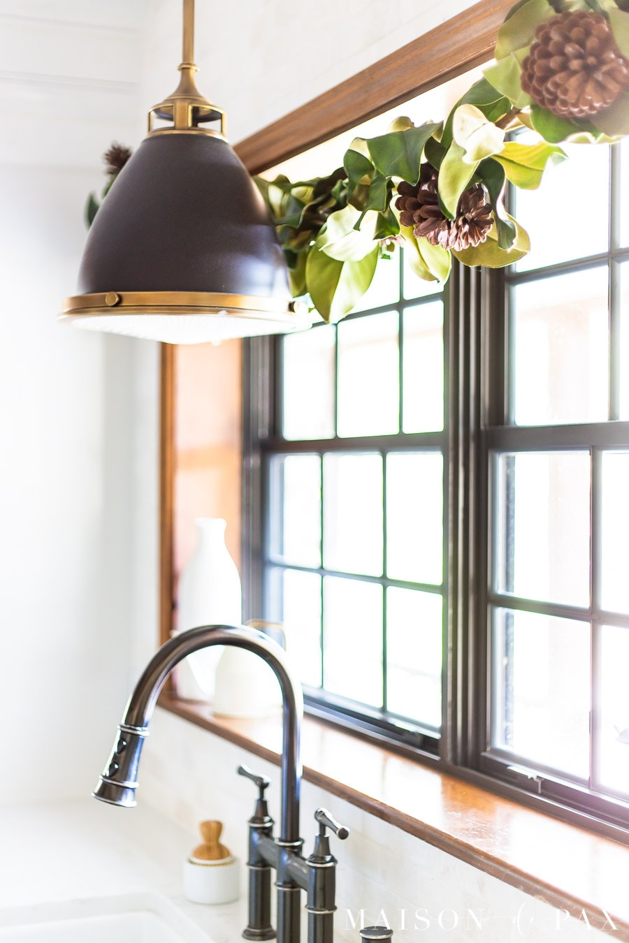 magnolia leaf garland and pendant light over farm sink | Maison de Pax