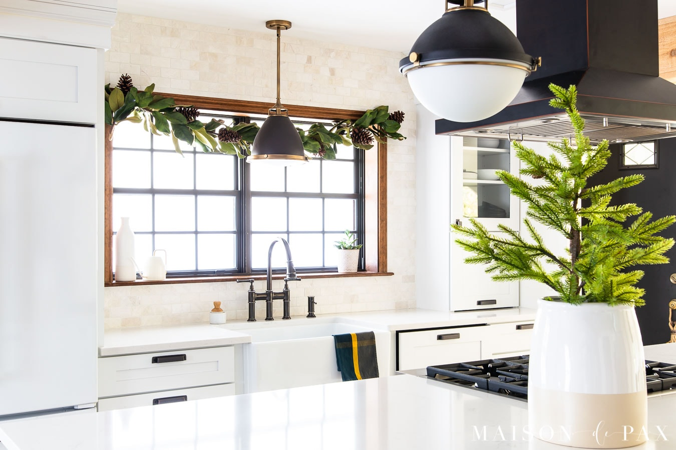 magnolia garland over farm sink with green plaid dish towel and mini tree on kitchen island | Maison de Pax