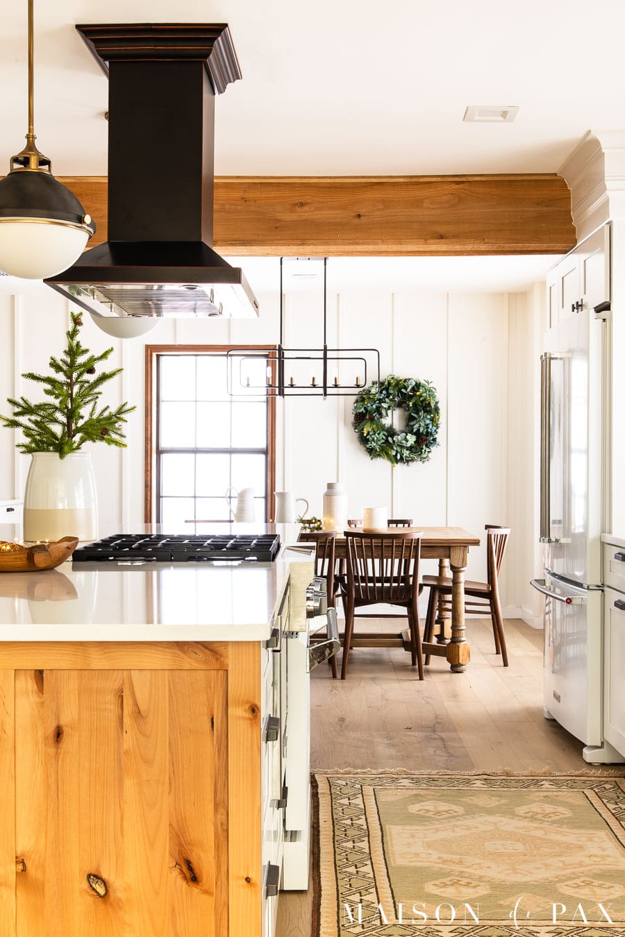 white and wood kitchen with rustic beams, farm table, and holiday greenery | Maison de Pax