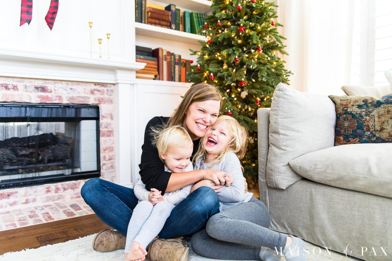 woman and daughters laughing in front of Christmas tree with white twinkle lights | Maison de Pax