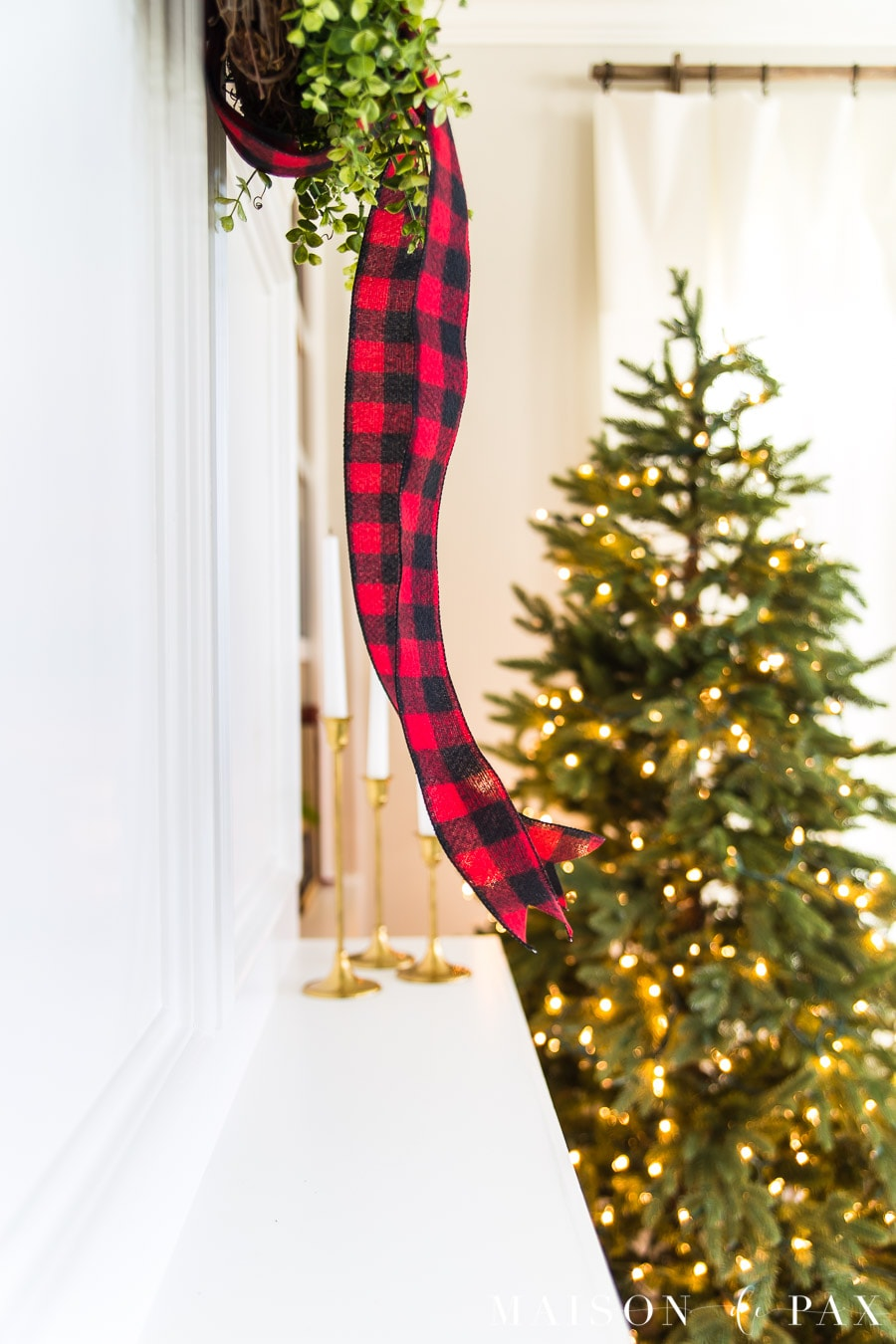 red buffalo check ribbon on green wreath by green christmas tree | maison de Pax