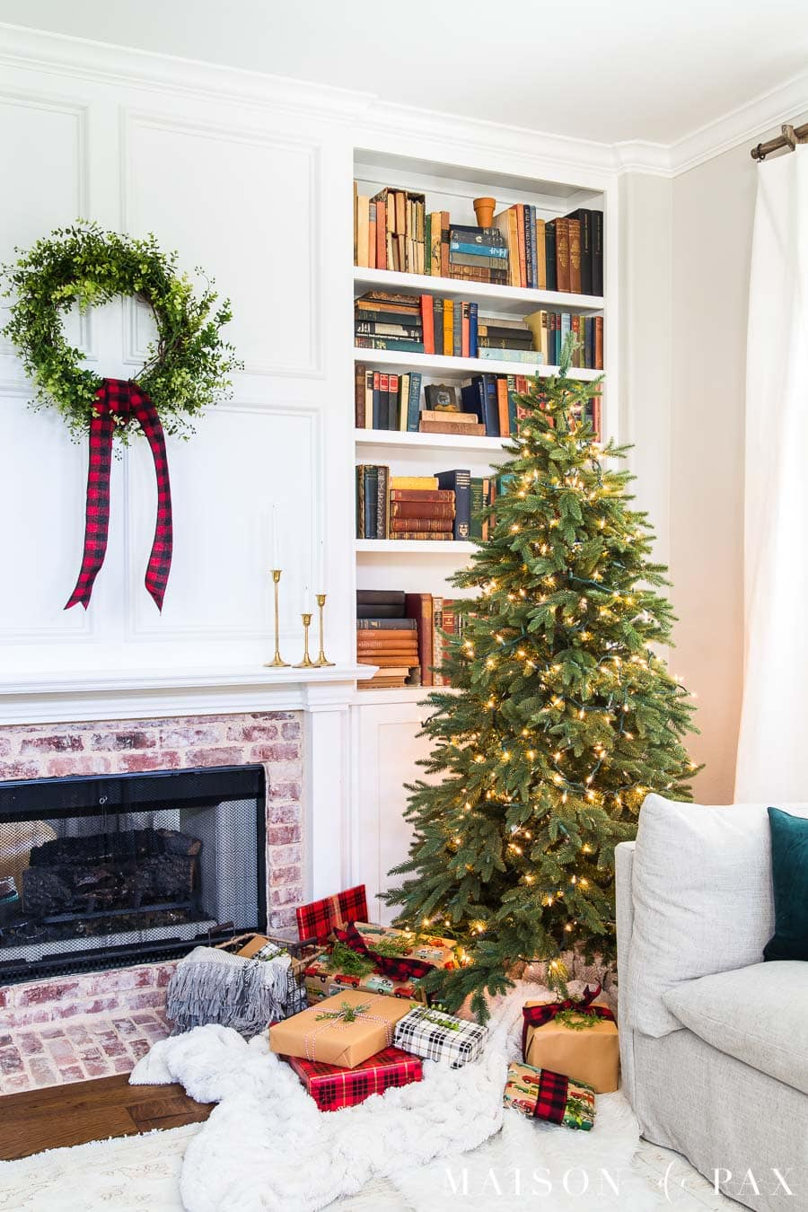 brick fireplace and white bookcase with red and green christmas decor | Maison de Pax