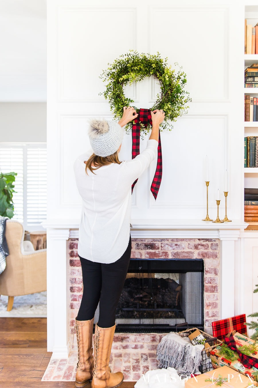 woman hanging wreath above mantel with red buffalo plaid ribbon | Maison de Pax