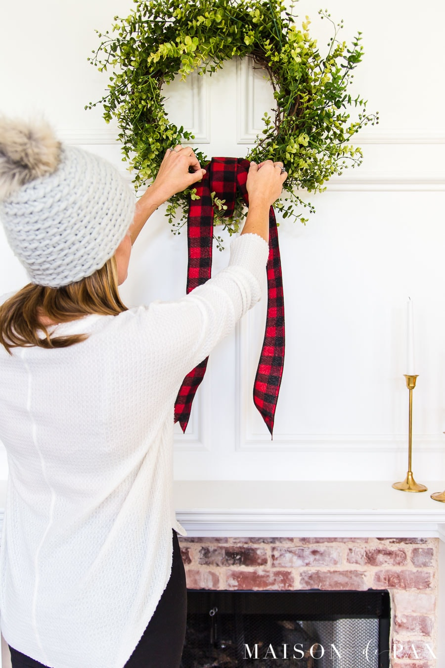 woman hanging red buffalo check ribbon on green wreath over mantel | Maison de Pax