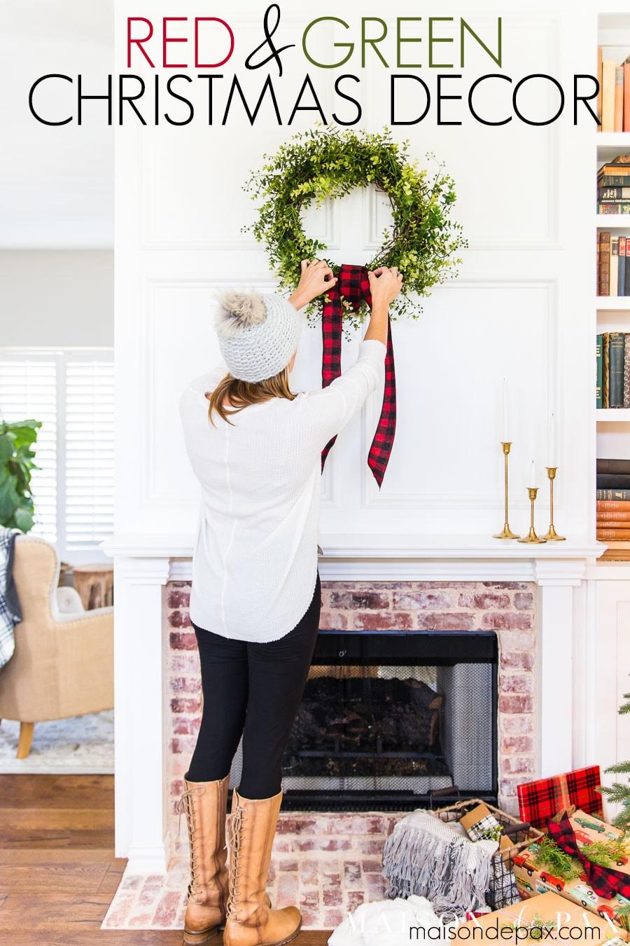 woman hanging DIY wreath above mantel | Maison de Pax