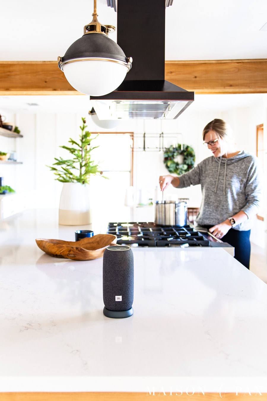 woman cooking in background with little bluetooth speaker in foreground | Maison de Pax