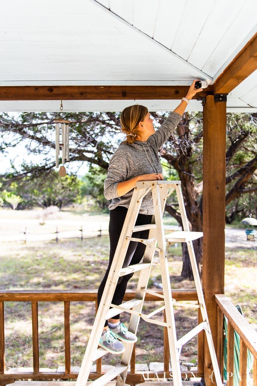 woman adjusting outdoor security camera   Maison de Pax