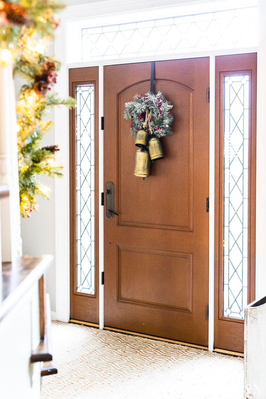 frosted wreath and gold bells on front door | Maison de Pax