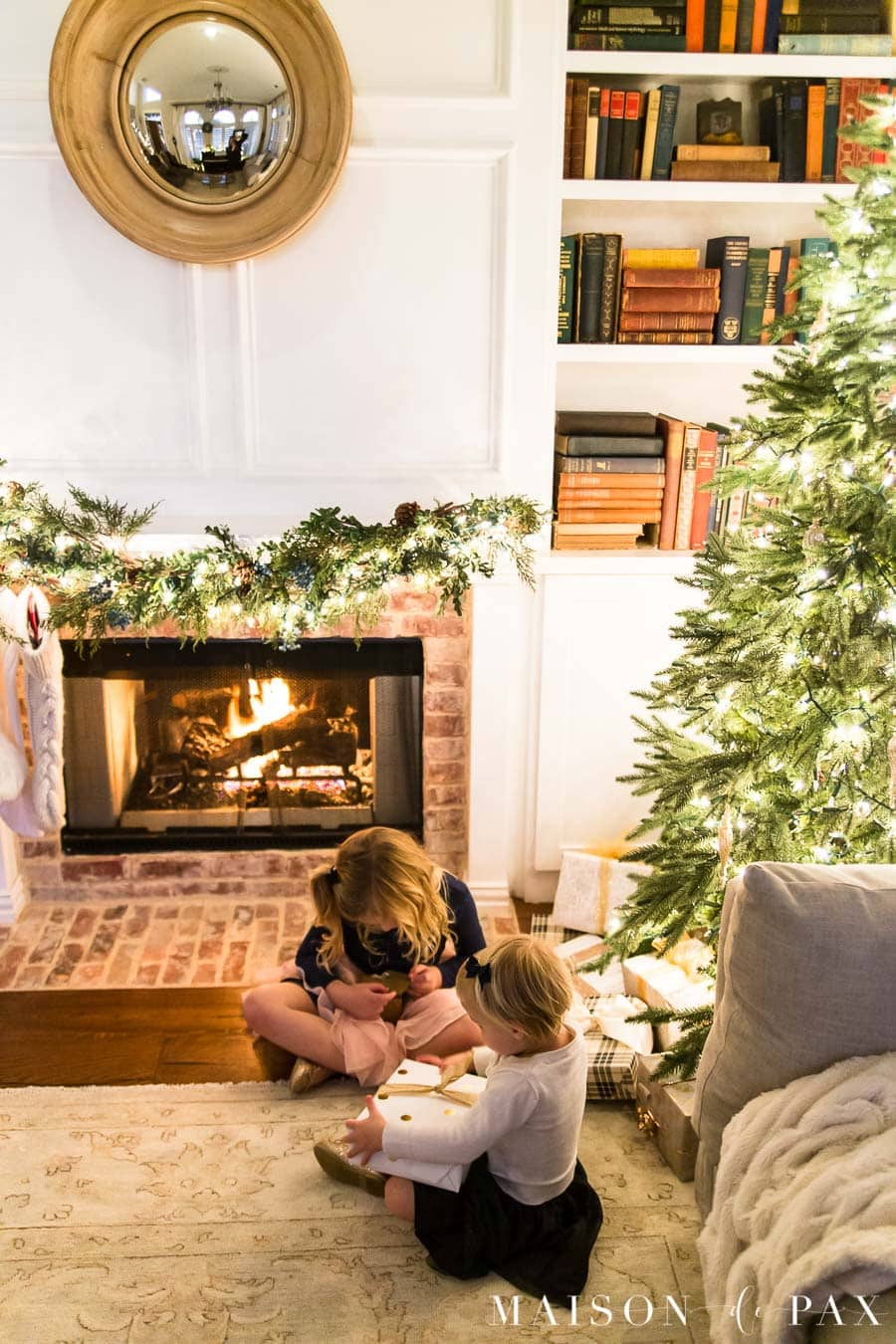 girls looking at presents under Christmas tree by fireplace | Maison de Pax