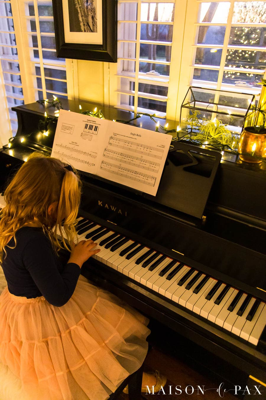 girl playing jingle bells on piano with Christmas lights | Maison de Pax