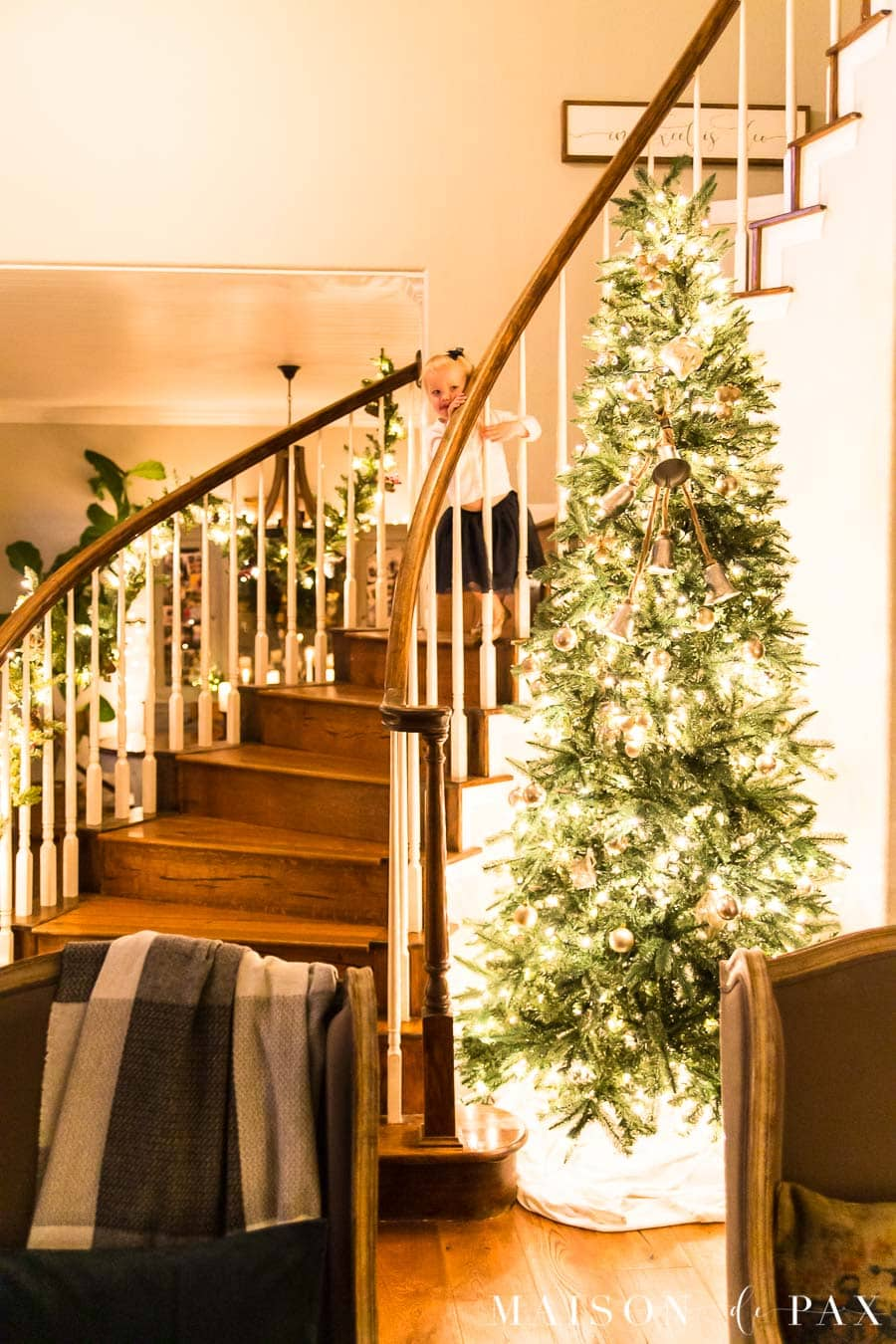 little girl on stairs beside huge lit Christmas tree | Maison de Pax