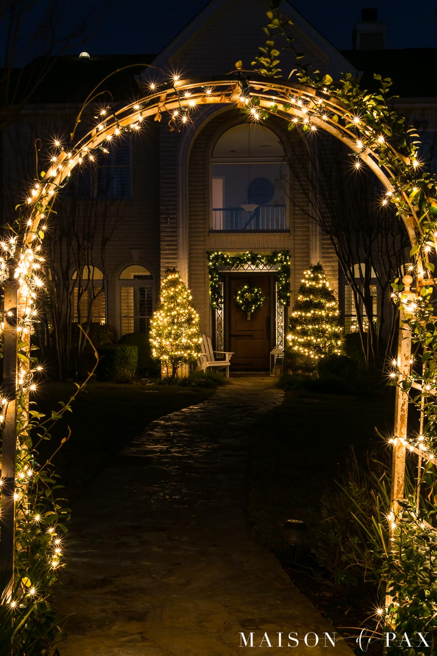 lit archway in front yard of house lit up with Christmas lights | Maison de Pax
