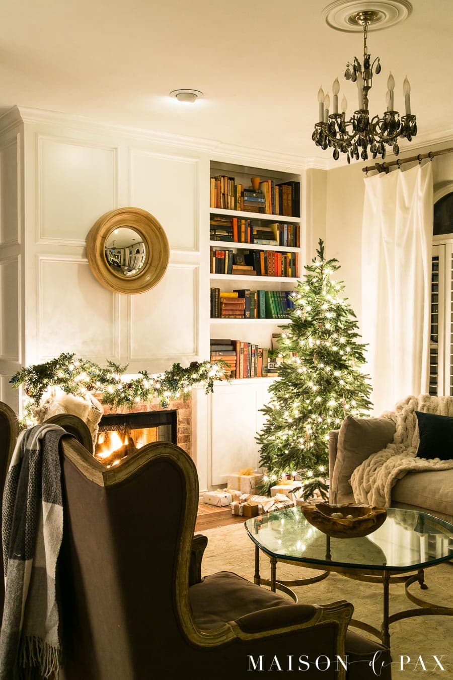 blazing fire, twinkle lights, and christmas tree in living room | Maison de Pax