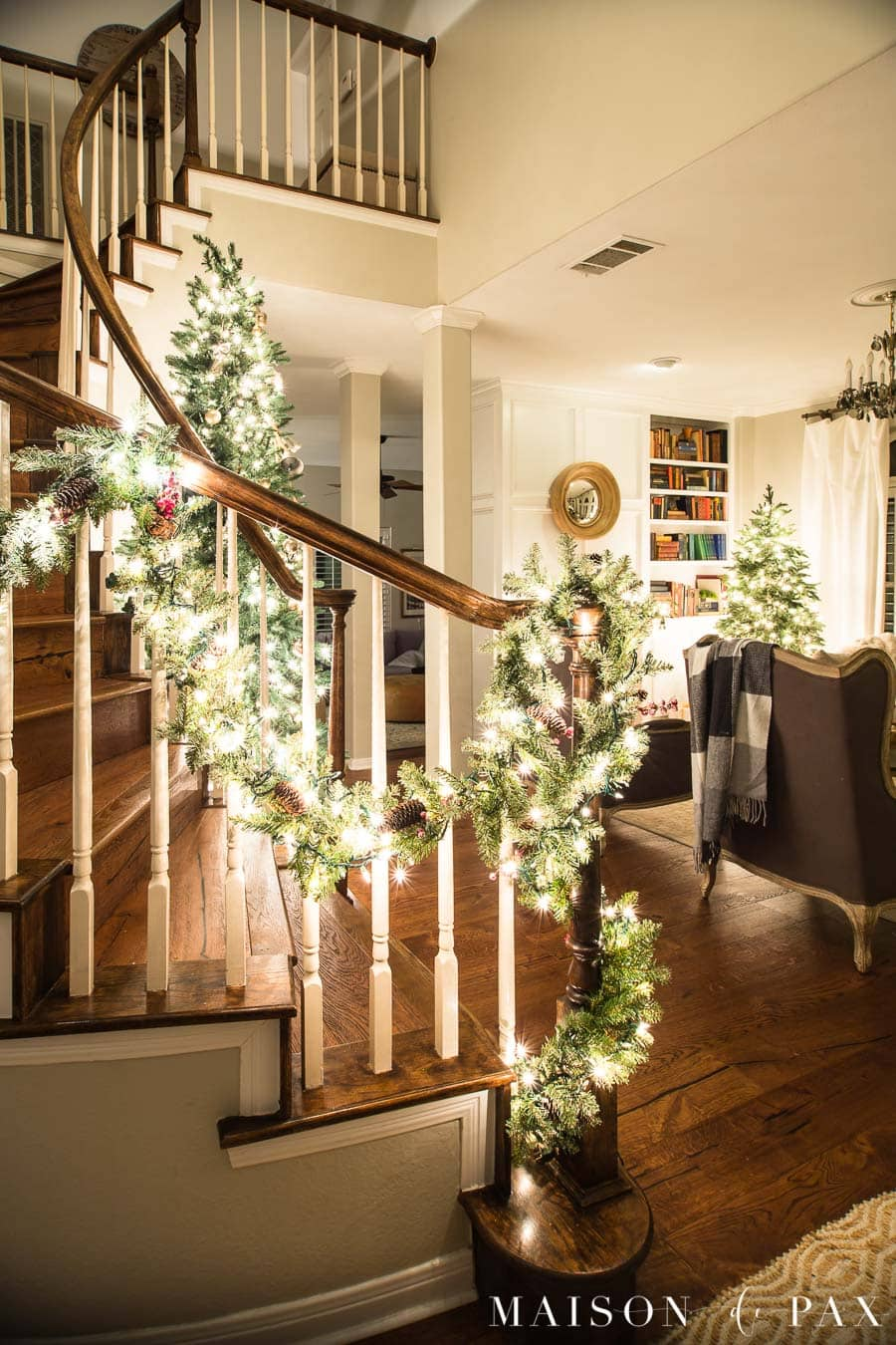 curved stairwell garland with christmas lights | Maison de Pax